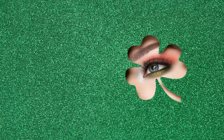 Conceptual photo of St. Patrick's Day. The Eye of the Young Beautiful Woman with Bright Golden Shadows and Expressive Eyebrows, Looks in the Shamrock Leaves Pattern out of Green Paper