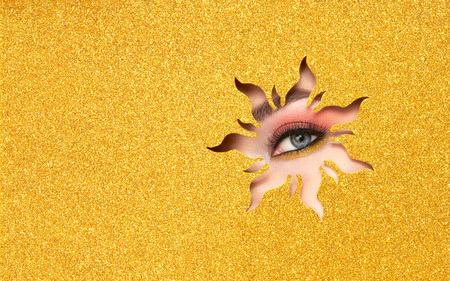 The Eyes of the Young Beautiful Woman with Bright Pink Shadows and Expressive Eyebrows, Looks in the Solar Shaped Pattern out of Yellow Paper. Yellow Sun. Summer Patterns. Advertising Banner Standard-Bild