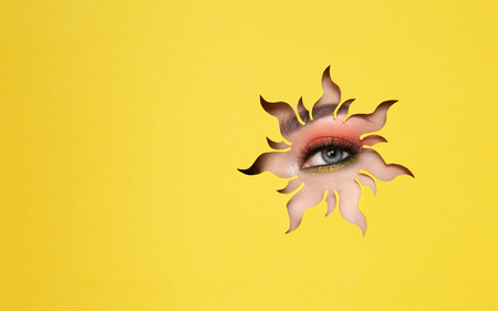 The Eyes of the Young Beautiful Woman with Bright Pink Shadows and Expressive Eyebrows, Looks in the Solar Shaped Pattern out of Yellow Paper. Yellow Sun. Summer Patterns. Advertising Banner Stock fotó