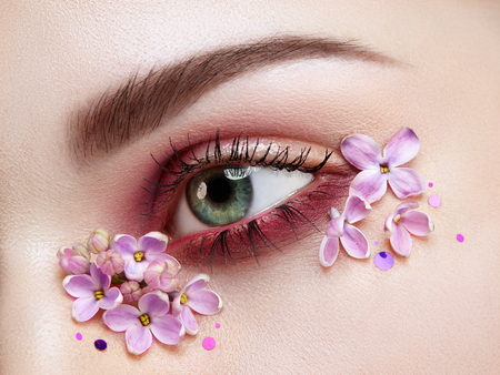 Eye makeup woman with a lilac flowers. Spring makeup. Beauty fashion. Eyelashes. Cosmetic Eyeshadow. Make-up detail. Creative woman floral make-up. Lilac petals