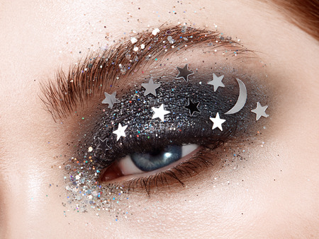 Mujer de maquillaje de ojos con estrellas decorativas. Maquillaje perfecto. Moda de belleza. Pestañas postizas. Sombra de ojos cosmética. Detalle de maquillaje. Delineador de ojos. Maquillaje creativo el cielo nocturno con estrellas.
