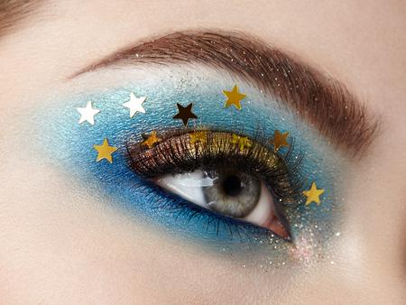 Kobieta makijaż oczu z ozdobnymi gwiazdami. Idealny makijaż. Moda uroda. Sztuczne rzęsy. Kosmetyczny cień do powiek. Detal makijażu. Kredka do oczu. Kreatywny makijaż nocne niebo z gwiazdami