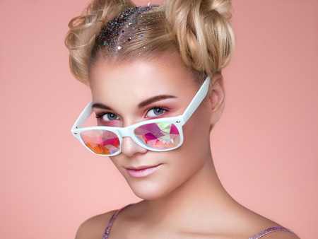 Portrait of Beautiful young Woman with Colored Glasses. Beauty Fashion. Perfect Make-up. Colorful Decoration. Hair Curled into a Bun Reklamní fotografie