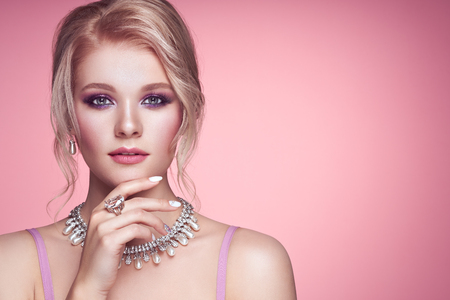 Portrait Beautiful Blonde Woman with Jewelry. Model Girl with Pearl Manicure on Nails. Elegant Hairstyle. Precious Stones and Silver. Beauty and Fashion Accessories. Perfect Make-Up. Pink Background Reklamní fotografie