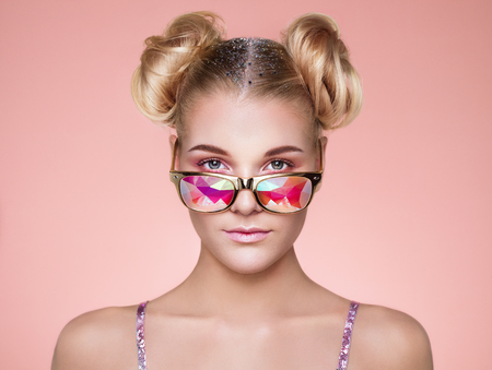 Ritratto di bella giovane donna con gli occhiali colorati. Moda di bellezza. Trucco perfetto. Decorazione colorata. Capelli arricciati in una crocchia Archivio Fotografico