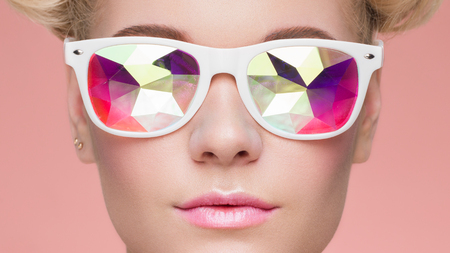 Portrait of Beautiful young Woman with Colored Glasses. Beauty Fashion. Perfect Make-up. Colorful Decoration. Holographic sunglasses. Coral color