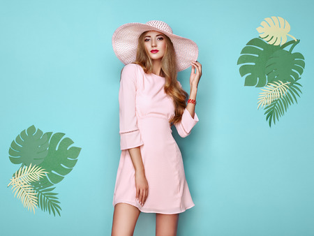 Portrait of Fashion Young woman in Pink Dress. Lady in Stylish Summer Outfit. Girl Posing on a turquoise Background. Stylish Hairstyle. Model On the background of Tropical Leaves Reklamní fotografie