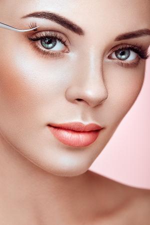 Beautiful Woman with Extreme Long False Eyelashes. Eyelash Extensions. Makeup, Cosmetics. Beauty, Skincare. Woman Glues Eyelashes Reklamní fotografie