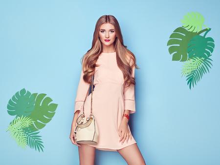Portrait de mode jeune femme en robe rose. Dame en tenue d'été élégante. Fille posant sur un fond bleu. Coiffure élégante. Modèle sur fond de feuilles tropicales
