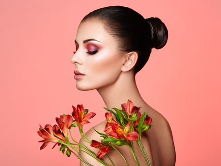 Portrait of beautiful young woman with Alstroemeria flowers. Brunette woman with luxury makeup. Perfect skin. Eyelashes. Cosmetic eyeshadow. Red flowers. Coral color
