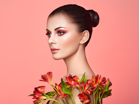 Portrait of beautiful young woman with Alstroemeria flowers. Brunette woman with luxury makeup. Perfect skin. Eyelashes. Cosmetic eye shadow. Red flowers. Coral color