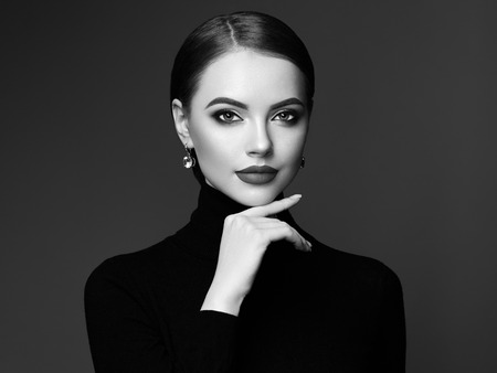 Beautiful Young Woman with Clean Fresh Skin. Perfect Makeup. Beauty Fashion. Plump Lips. Cosmetic Eye shadow. Smooth Hair. Girl in Black Turtleneck. Black and white photo
