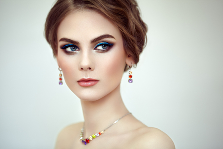 Portrait Beautiful Woman with Jewelry. Fashion Makeup and Cosmetics. Elegant Hairstyle. Blue Make-up Arrows. Beauty and Accessories