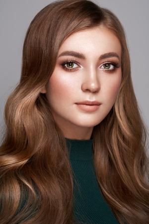 Donkerbruin meisje met lang gezond en glanzend krullend haar. Verzorging en schoonheid Haarproducten. Mooie modelvrouw met golvend kapsel. Perfecte make-up Stockfoto