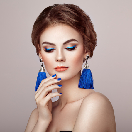 Beautiful Woman with Large Earrings Tassels jewelry Blue color. Perfect Makeup and Elegant Hairstyle. Blue Make-up Arrows. Blue nails manicure