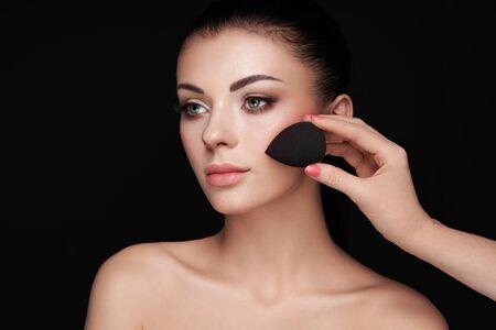 Artista de maquillaje aplica tono de piel. Rostro de mujer hermosa. Maquillaje perfecto. Base para el cuidado de la piel. Artista de maquillaje de esponja