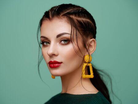 Chica morena con maquillaje perfecto. Mujer hermosa modelo con peinado rizado. Productos para el cuidado y la belleza del cabello. Dama con cabello trenzado. Modelo con joyas. Fondo turquesa
