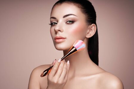 Beautiful Woman applies Skin Tone with Brush. Beautiful Woman face. Perfect Makeup. Skincare Foundation. Brushes Makeup Artist 스톡 콘텐츠