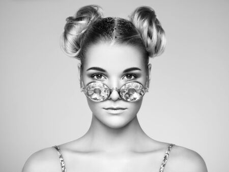 Portrait of beautiful young woman in sunglasses. Beauty Fashion. Black and white photo. Hair Curled into a Bun