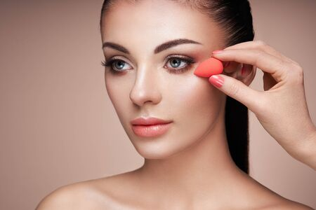 Makeup artist applies skintone. Beautiful woman face. Perfect makeup. Skincare foundation. Sponge makeup artist Reklamní fotografie