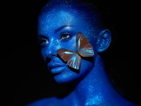 Fashion model woman in blue bright sparkles and neon lights posing in studio.  Portrait of beautiful sexy woman with blue butterfly. Art design colorful glitter glowing make up Stock fotó - 127785140
