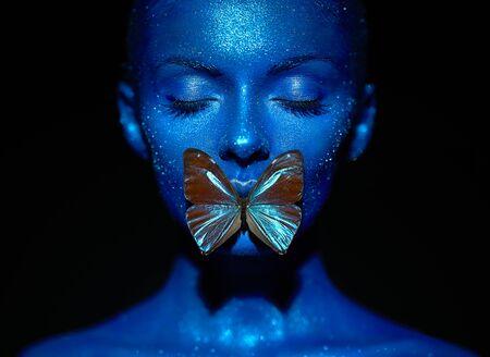 Mujer modelo de moda en destellos brillantes azules y luces de neón posando en el estudio. Retrato de mujer hermosa con mariposa azul. Diseño de arte colorido brillo brillante maquillaje