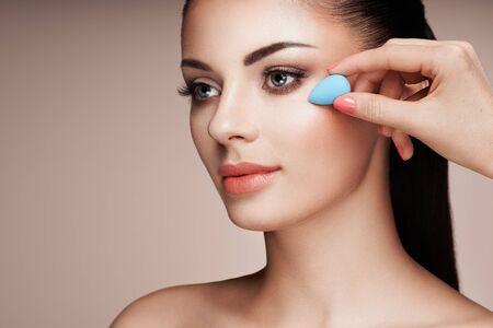 Makeup artist applies skintone. Beautiful woman face. Perfect makeup. Skincare foundation. Sponge makeup artist Stock fotó