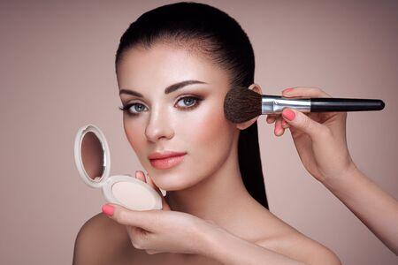 Beautiful Woman applies Skin Tone with Brush. Beautiful Woman face. Perfect Makeup. Skincare Foundation. Brushes Makeup Artist Stock fotó