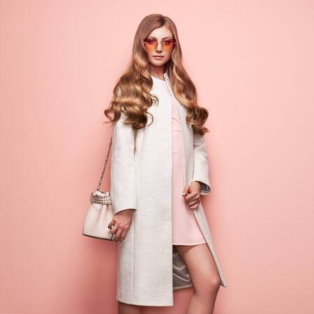 Young elegant woman in trendy white coat. Blond hair, pink dress, isolated studio shot. Fashion autumn lookbook. Model woman with handbag 免版税图像