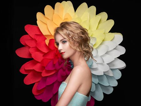 Beautiful woman on the background of a large flower. Beauty summer model girl with rainbow chrysanthemum. Young woman with elegant hairstyle and makeup. Fashion photo