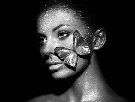 Fashion model woman in bright sparkles and lights posing in studio. Portrait of beautiful woman with butterfly. Art design glitter glowing make up. Black and white photography