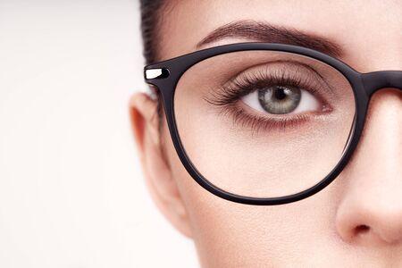 Female eye with long eyelashes in eyeglasses. Model in glasses. Vision correction. Poor eyesight. Spectacle frame. Makeup, cosmetics, beauty. Close up, macro Imagens