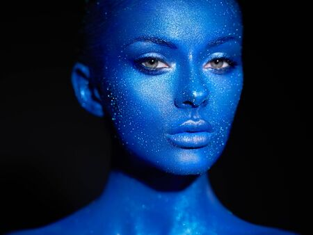 Fashion model woman in blue bright sparkles and neon lights posing in studio. Portrait of beautiful woman. Art design colorful glitter glowing make up