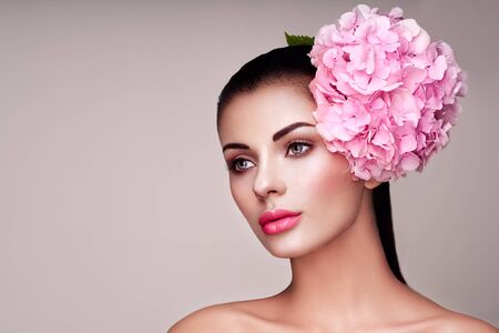 Portret model decorated with large pink flower on the head. Brunette woman with luxury makeup. Perfect skin. Eyelashes. Cosmetic eyeshadow Stock Photo