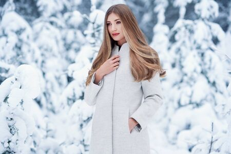 Fashion young woman in the winter forest. Young elegant model in trendy white coat in nature. Blonde girl with long smooth hair Stock Photo