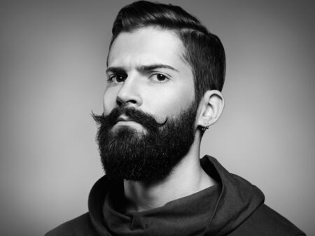 Portrait of handsome man with beard and mustache. Close-up image of serious brutal bearded man on dark background. Black and white photography Foto de archivo