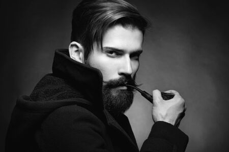 Brutal man with a beard and mustache Smoking a pipe. Close-up image of serious bearded man on dark background. Black and white photography Stock Photo