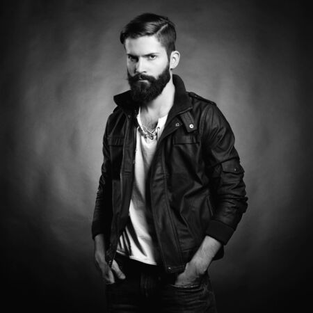 Portrait of handsome man with beard and mustache. Close-up image of serious brutal bearded man on dark background. Black and white photography