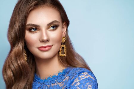 Brunette girl with perfect makeup. Beautiful model woman with curly hairstyle. Care and beauty hair products. Lady with fashionable gold makeup. Model with jewelry on blue background