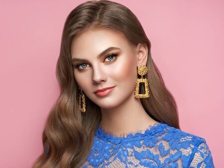 Brunette girl with perfect makeup. Beautiful model woman with curly hairstyle. Care and beauty hair products. Lady with fashionable gold makeup. Model with jewelry on pink background