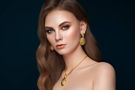 Brunette girl with perfect makeup. Beautiful model woman with curly hairstyle. Care and beauty hair products. Lady with fashionable gold makeup. Model with jewelry on dark blue background
