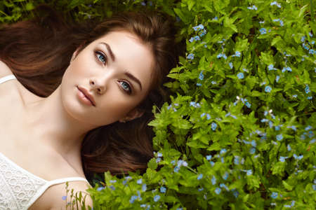 Portrait of a beautiful young woman in summer garden. Girl on nature. Spring flowers. Fashion beauty Standard-Bild