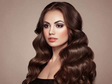 Brunette Girl with Long Healthy and Shiny Curly Hair.