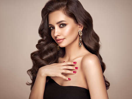 Brunette girl with perfect makeup. Smiling beautiful model woman with long curly hairstyle. Care and beauty hair products. Red nails manicure