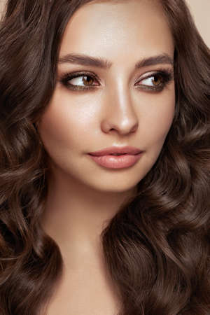 Brunette girl with perfect makeup. Smiling beautiful model woman with long curly hairstyle. Care and beauty hair products. Standard-Bild