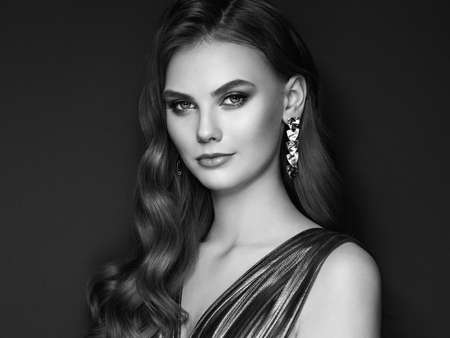 Brunette girl with perfect makeup. Beautiful model woman with curly hairstyle. Care and beauty hair products. Lady with fashionable makeup. Model with jewelry on dark background Standard-Bild