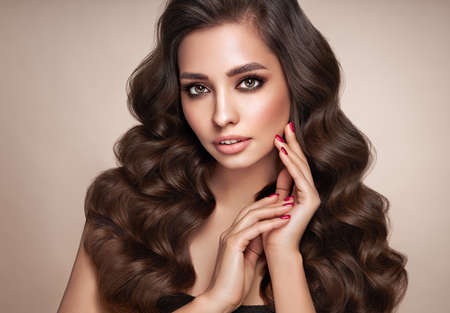 Brunette girl with perfect makeup. Smiling beautiful model woman with long curly hairstyle. Care and beauty hair products. Red nails manicure Standard-Bild