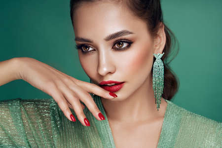 Portrait beautiful woman with jewelry. Brunette girl with long smooth hair. Beauty fashion. Model girl with red color manicure on nails in turquoise evening dress