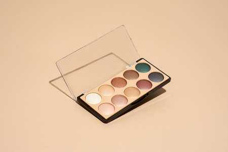 Make-up palette floating over a beige background. Professional multicolor eye shadow make-up palette. Cosmetic products