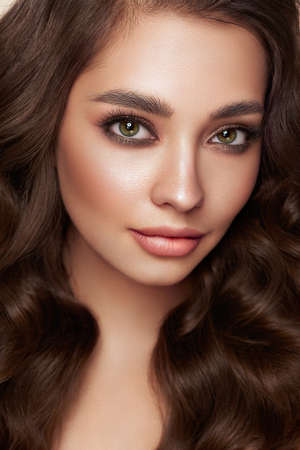 Brunette girl with perfect makeup. Smiling beautiful model woman with long curly hairstyle. Care and beauty hair products. Model in blue dress Banque d'images